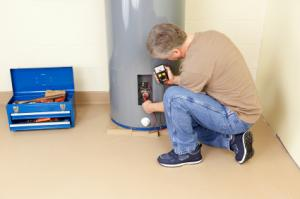 a Rockwall plumber is inspecting a water heater